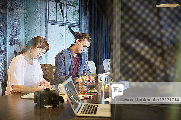 Creative business people writing while sitting at conference table in office