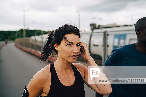 Young female athlete looking away while jogging with male friend on footbridge
