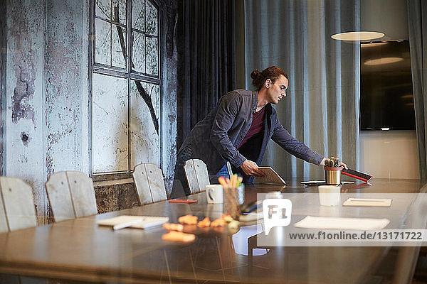 Junger kreativer Geschäftsmann führt Tagebuch auf Konferenztisch im Büro