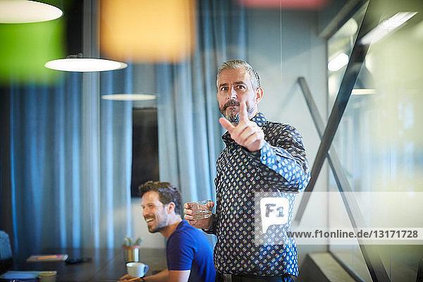 Ein reifer Geschäftsmann  der während einer Besprechung im Büro auf einen auf Glas geklebten Zettel zeigt