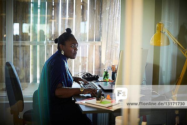 Seitenansicht einer Geschäftsfrau  die am Computerschreibtisch im Kreativbüro arbeitet