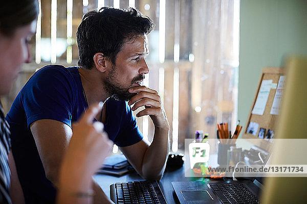 Männliche und weibliche Mitarbeiter diskutieren am Computerschreibtisch im Kreativbüro
