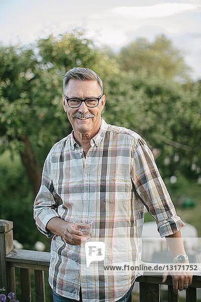 Porträt eines lächelnden älteren Mannes mit einem Trinkglas in der Hand auf der Veranda stehend