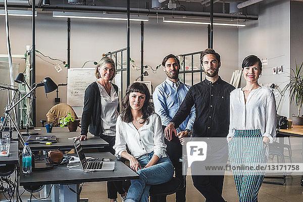 Porträt von selbstbewussten Mitarbeitern am Schreibtisch im Kreativbüro