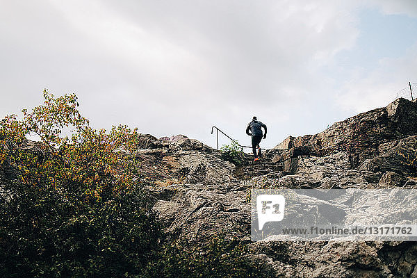 Low angle view of male athlete climbing rocks on hill against sky