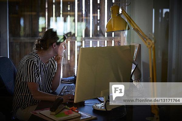 Kreative Geschäftsfrau  die im Büro am Computerschreibtisch arbeitet