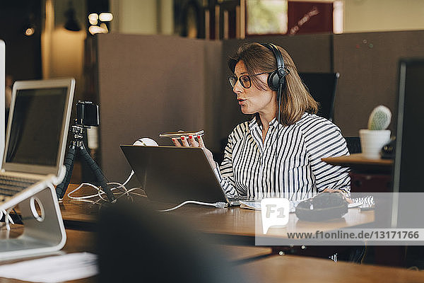 Mature businesswoman wearing headphones while talking on mobile phone in office