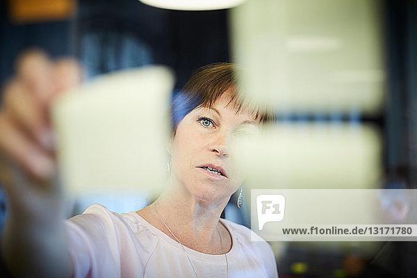 Reife Geschäftsfrau klebt Klebezettel auf Glas im Kreativbüro