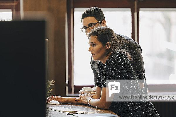 Mittlerer erwachsener Geschäftsmann und Geschäftsfrau diskutieren in neuem Büro