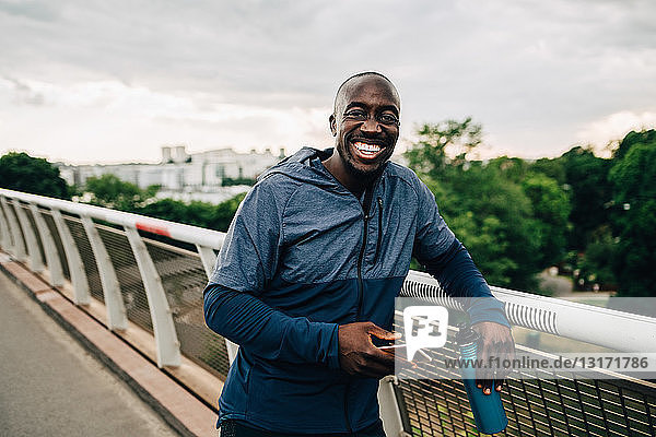 Portrait of cheerful sportsman holding mobile phone and bottle while standing on footbridge