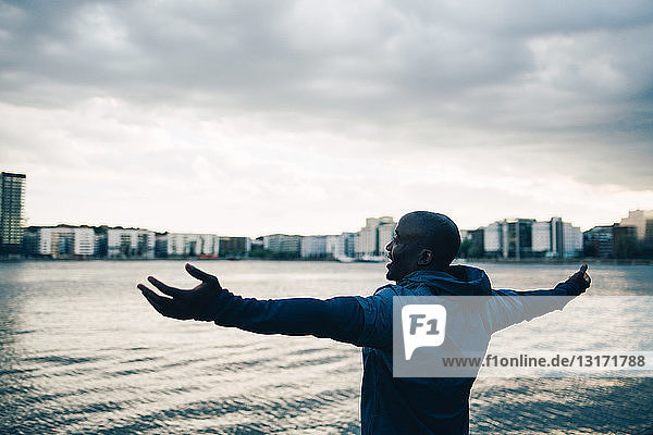 Male athlete standing with arms outstretched by sea against sky in city