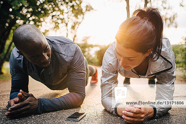 Male and female athletes looking at mobile phone while doing planks on road in park