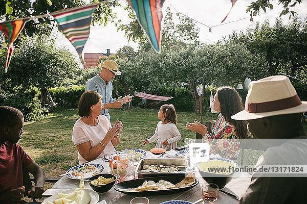Familie applaudiert beim Tanz eines älteren Mannes und eines Mädchens während einer Gartenparty