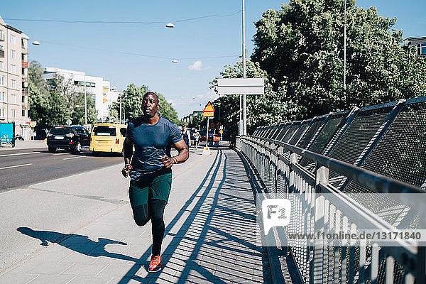 Full length of male athlete jogging on sidewalk at bridge in city