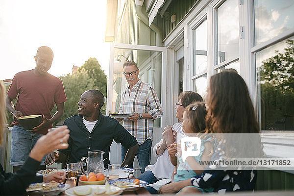 Glückliche Mehrgenerationen-Familie genießt Mittagessen auf der Veranda