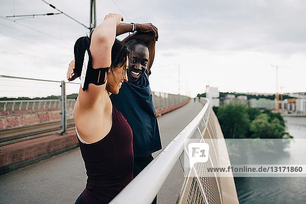 Smiling male and female athletes stretching hands on footbridge over sea against sky