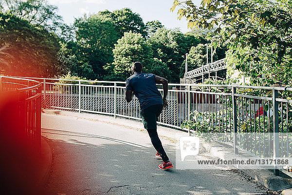 Rear view of sportsman jogging on footbridge in city