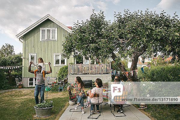 Familie betrachtet Mann mit Tochter auf den Schultern während Gartenparty