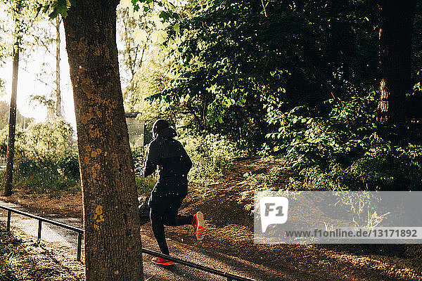 Full length of male athlete running on footpath in park