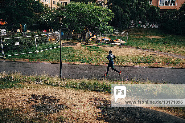 Full length of male athlete jogging on road in city