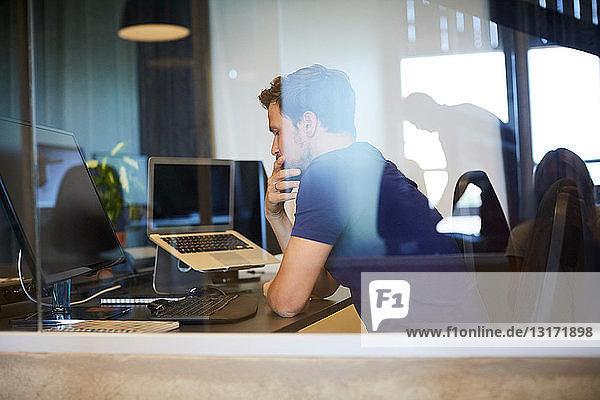 Geschäftsmann am Computerschreibtisch sitzend durch Glas im Büro gesehen