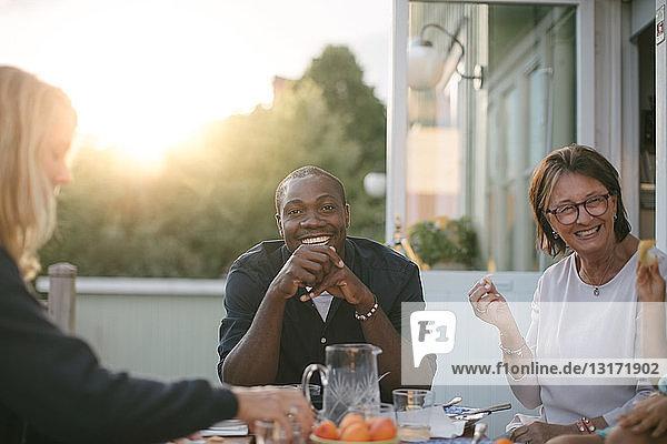 Lächelnde Mehrgenerationen-Familie beim Mittagessen am Tisch auf der Veranda