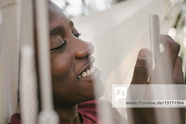 Lächelnder Junge benutzt Mobiltelefon  während er sich auf der Hängematte entspannt