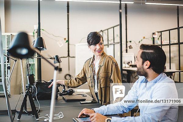 Kreative Geschäftsleute unterhalten sich während der Arbeit am Schreibtisch im Büro