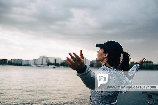 Weibliche Athletin steht mit ausgestreckten Armen am Meer gegen den Himmel in der Stadt