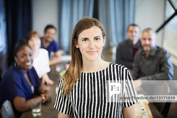 Porträt einer selbstbewussten Geschäftsfrau im Stehen  während ihre Kollegen im Hintergrund im Amt sind