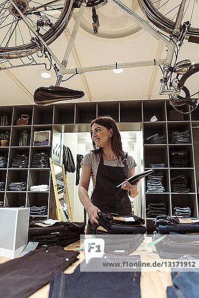 Lächelnder Besitzer mit digitalem Tablet  das die Bestellung in einer Boutique analysiert