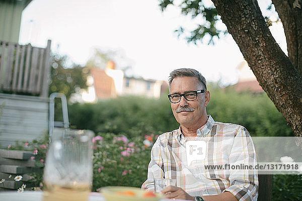 Porträt eines lächelnden älteren Mannes am Tisch im Hinterhof
