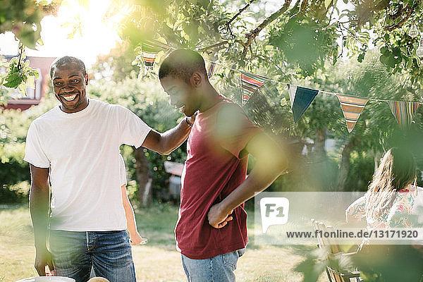 Lächelnder Vater schaut weg  während er während der Party im Hinterhof beim Sohn steht