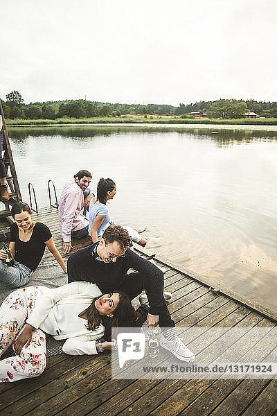 Paar mit Freunden auf dem Bootssteg über dem See während eines Wochenendausflugs