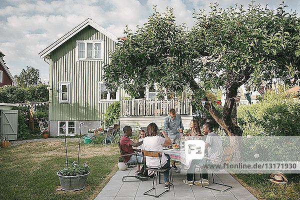 Mehrgenerationen-Familie genießt Getränke auf der Terrasse während einer Gartenparty