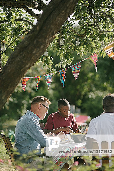 Junge isst während der Gartenparty mit Vater und Großvater auf der Terrasse zu Mittag