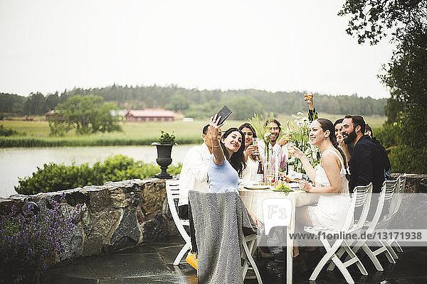 Lächelnde Frau  die sich während einer Dinner-Party im Hinterhof mit Freunden trifft