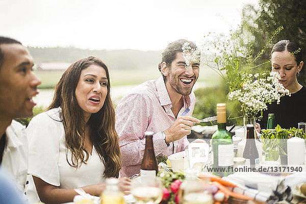 Happy friends enjoying dinner at table in backyard during party