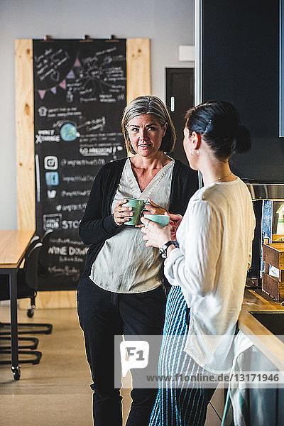 Weibliche Kollegen unterhalten sich beim Kaffee in der Büro-Cafeteria