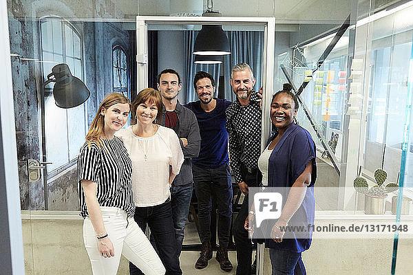 Porträt von lächelnden Geschäftsleuten  die während des kreativen Büros im Büro stehen
