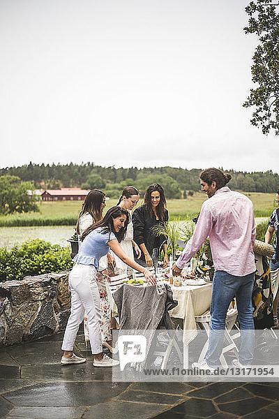 Multiethnische Freunde lächeln beim Stehen um den Esstisch im Hinterhof während einer Dinnerparty