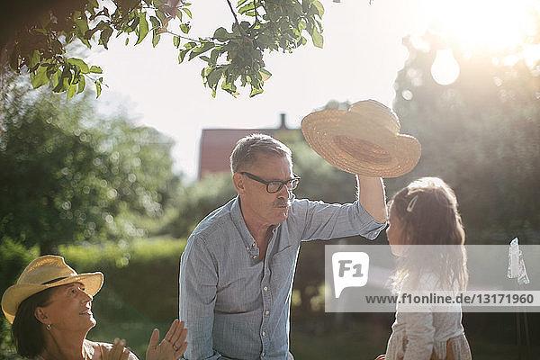 Frau klatscht und schaut älteren Mann an  der an einem sonnigen Tag im Garten einen Strohhut über seine Enkelin hält