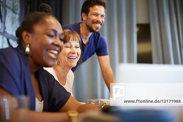 Kreative Geschäftsleute lächeln während einer Besprechung im Büro