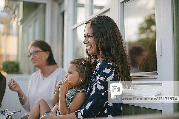 Lächelnde Mutter mit Tochter isst Obst  während sie von einer älteren Frau auf der Veranda sitzt