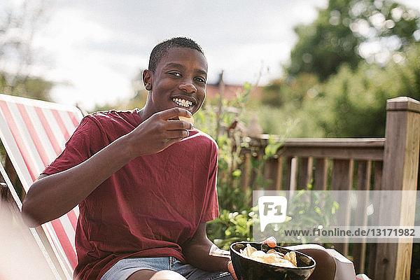 Porträt eines lächelnden Jungen  der einen Snack isst  während er auf der Veranda sitzt