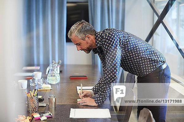 Seitenansicht eines reifen Geschäftsmannes  der auf Papier schreibt  während er im Büro am Konferenztisch steht