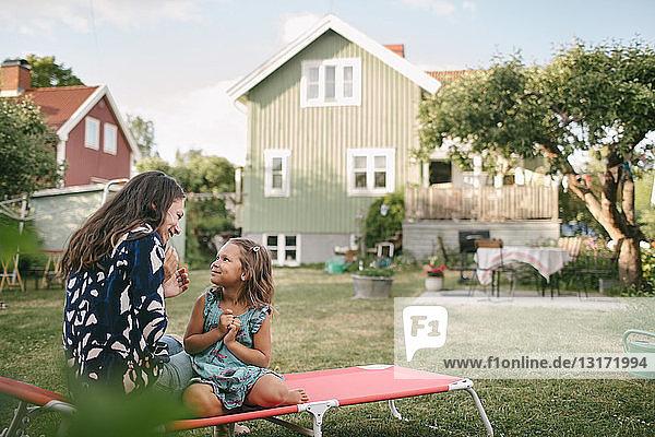 Lächelnde Mutter und Tochter unterhalten sich  während sie auf einem Liegestuhl im Hinterhof sitzen