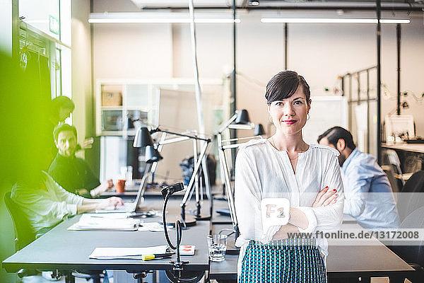 Porträt einer selbstbewussten Geschäftsfrau  die mit verschränkten Armen gegen den Schreibtisch steht