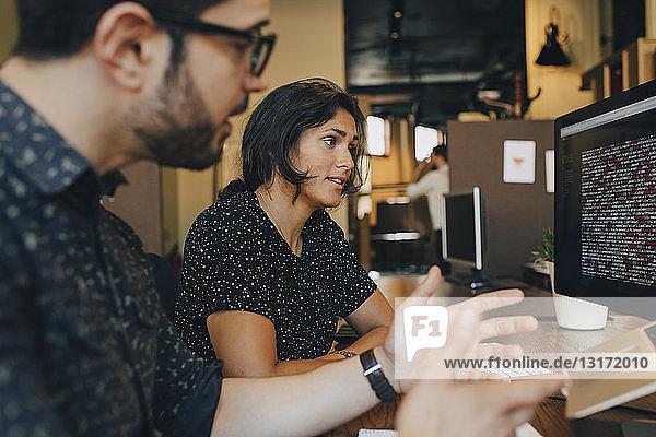 Computerprogrammiererin diskutiert mit ihrem Kollegen am Schreibtisch im Büro