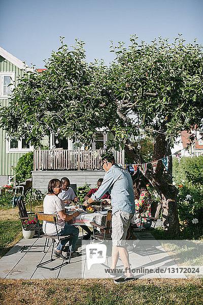 Mehrgenerationen-Familie isst während der Gartenparty gemeinsam auf der Terrasse zu Mittag